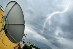 Parabolic antenna and lightning Stock Photos