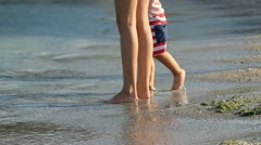 Lady feet and baby feet at the seashore, baby feet hits the water sea Stock Footage