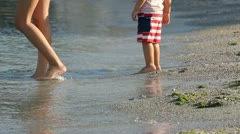 Mother feet going to the sea and hesitating child feet follow her Stock Footage