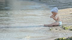 Baby boy sitting on the seashore waching the waves and fluttering his hands Stock Footage
