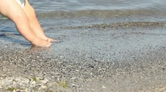 Baby feet trying to stand up and playing with water sea at the seashore Stock Footage