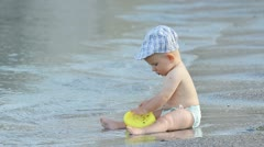 Little baby sitting on the sea shore loosing his toy taken by the waves Stock Footage