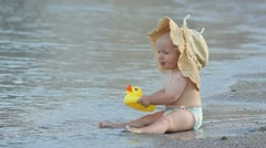 Little baby with a big hat tasting the toy Stock Footage