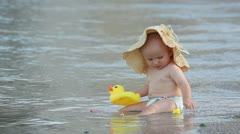Little baby with big hat sitting on the beach with a duck toy - stock footage