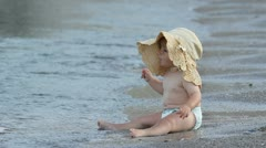 Sweet liitle baby girl sitting on the sea shore looking up Stock Footage