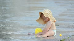 Litle baby with a big hat playing alone on the beach Stock Footage
