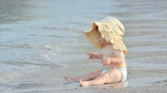 Little baby with a big hat enjoying the sea waves touch Stock Footage