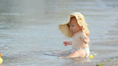 Cute baby looking hopeless to the toys taken by the sea waves Stock Footage