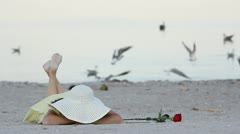 Young woman laying on the beach near a red rose and seaguls flying Stock Footage