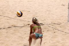 Woman bump passes a volleyball at the beach - stock photo