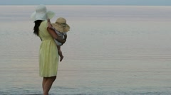 Mother and baby wearing hats on the beach Stock Footage