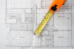 a measuring tape on top of house plans. - stock photo