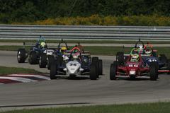 Group of Formula One Cars Racing around Corner Stock Photos