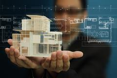 Stock Illustration of manholding a model of a house in his hands.