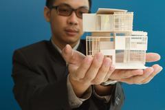 man holding a model of a house in his hands. - stock illustration