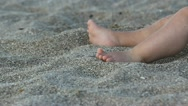 Baby feet and hands playing in the sand on the beach Stock Footage