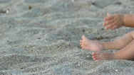 Little baby feet on the beach and hand playing with the sand Stock Footage