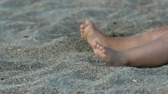 Baby feet rotating and adult hand playing with the sand Stock Footage
