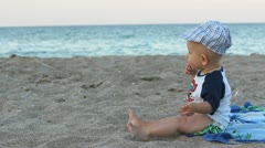 Happy little baby boy sitting on the beach sand and moving his hands and soles - stock footage
