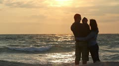 Lovely family resting on the beach and admiring the sunrise over the sea Stock Footage