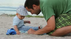 Father and son playing with the sand on the beach Stock Footage