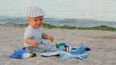 Crying baby boy sitting on the beach Stock Footage