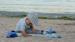 Child playing with sand and finding a shell on the beach Stock Footage