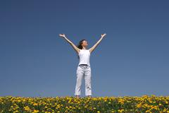 Young woman greets the sun - stock photo