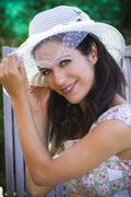 Beautiful young brunette in a summer garden with white hat Stock Photos