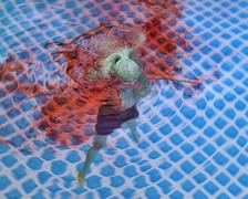 Blue colored Barbie doll, bleeding and drowning in water pool Stock Photos