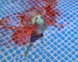 Stock Photo of Blue colored Barbie doll, bleeding and drowning in water pool