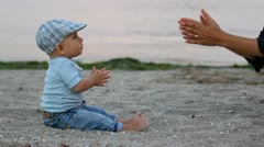 Child learning to clap his hands from his mother hand Stock Footage