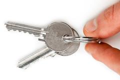 Finger holding set of keys - stock photo