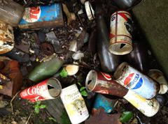 Pull-Top soda pop cans and beer cans in garbage trash pile, broken bottles Stock Photos