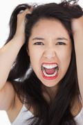Woman screaming and pulling her hair out - stock photo