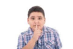portrait of beautiful little boy with silence gesture over white background - stock photo