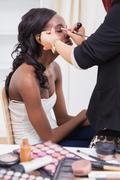 Stock Photo of Woman sitting while getting makeup done