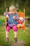 adorable girl swing with plush toy on playground in park - stock photo