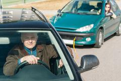 Man helping woman by pulling her car Stock Photos