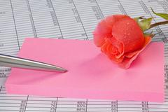 Rose and notepad on a spreadsheet Stock Photos