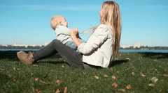 Baby funning with mother on the grass in park - stock footage