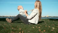 Baby funning with mother on the grass in park Stock Footage