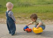 Stock Photo of two boys trying to repair a toy truck
