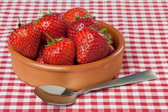 Stock Photo of dish of strawberries on red gingham tablecloth