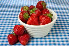 Bowl of strawberries on a blue gingham tablecloth Stock Photos