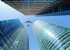 Airliner flying over skyscrapers Stock Photos