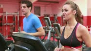 Stock Video Footage of Woman and man jogging on treadmills