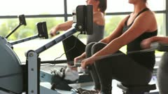 Women working out on rowing machine Stock Footage