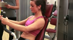 Woman on weights machine talking to trainer Stock Footage