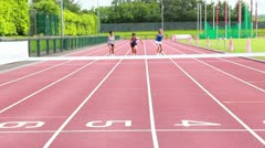 Three woman running on a track and crossing finish line Stock Footage